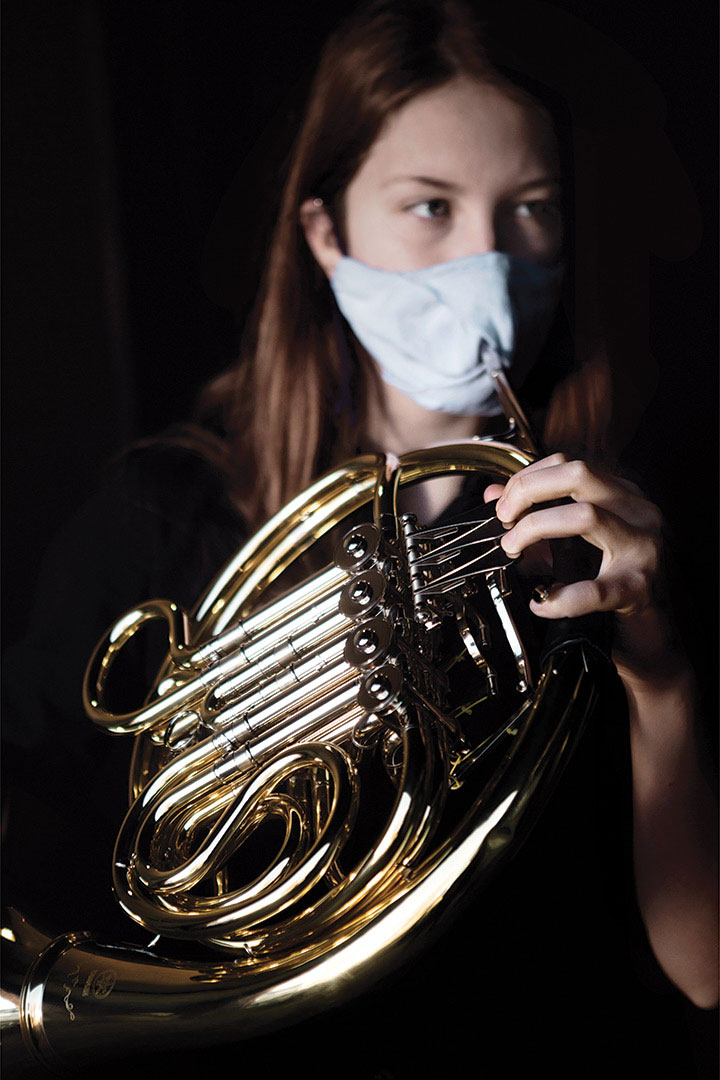 Masked student holds French horn with bell cover