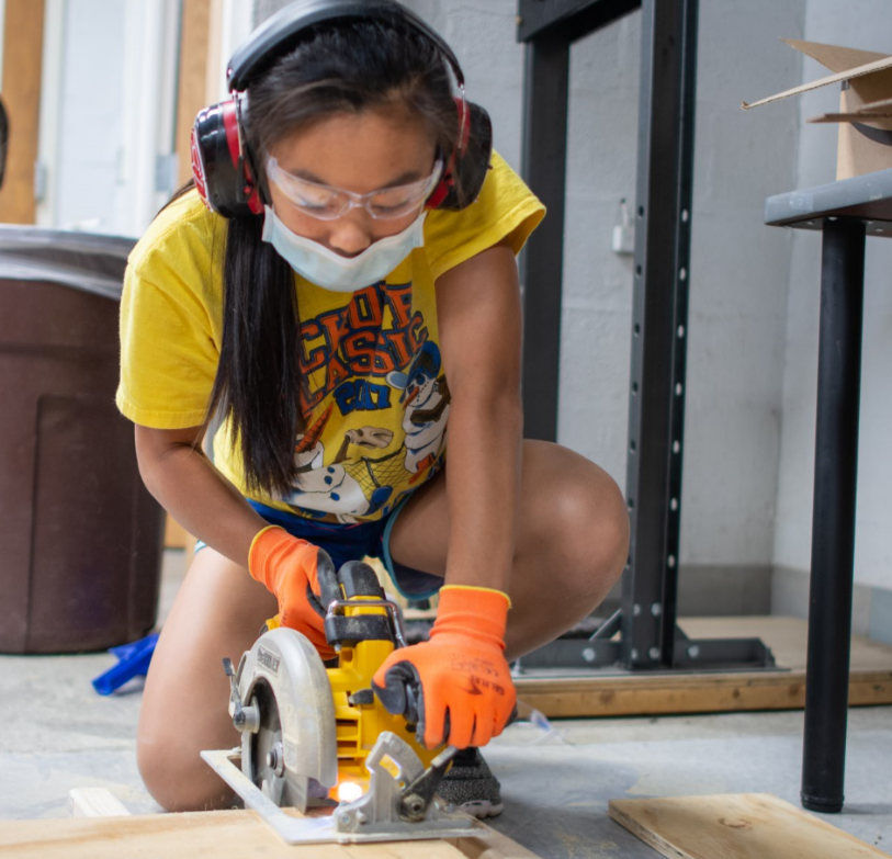 Girl using power saw in MPower Tools camp