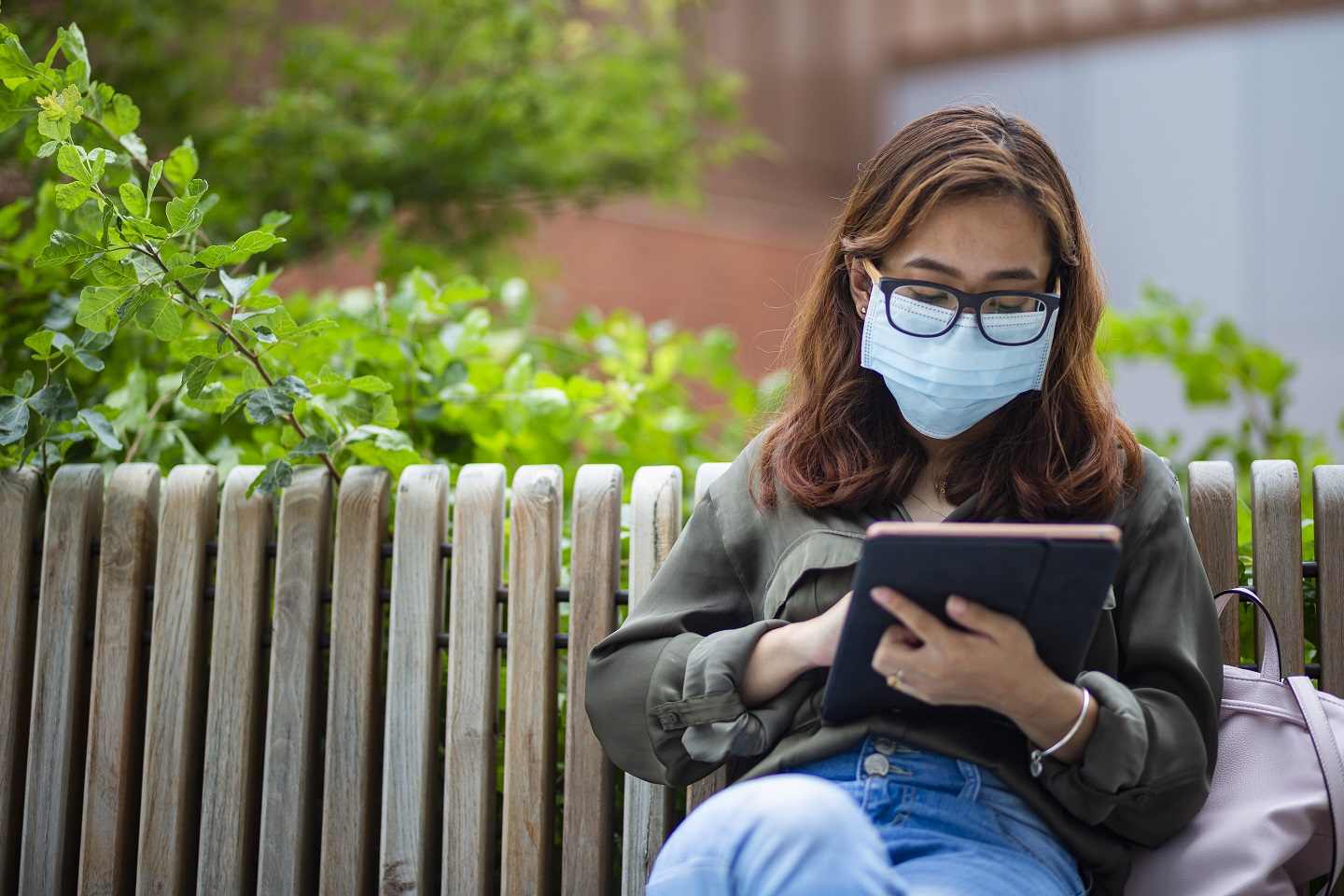 Student reading her tablet on the bench by the Brendan Iribe Center for Computer Science and Engineering