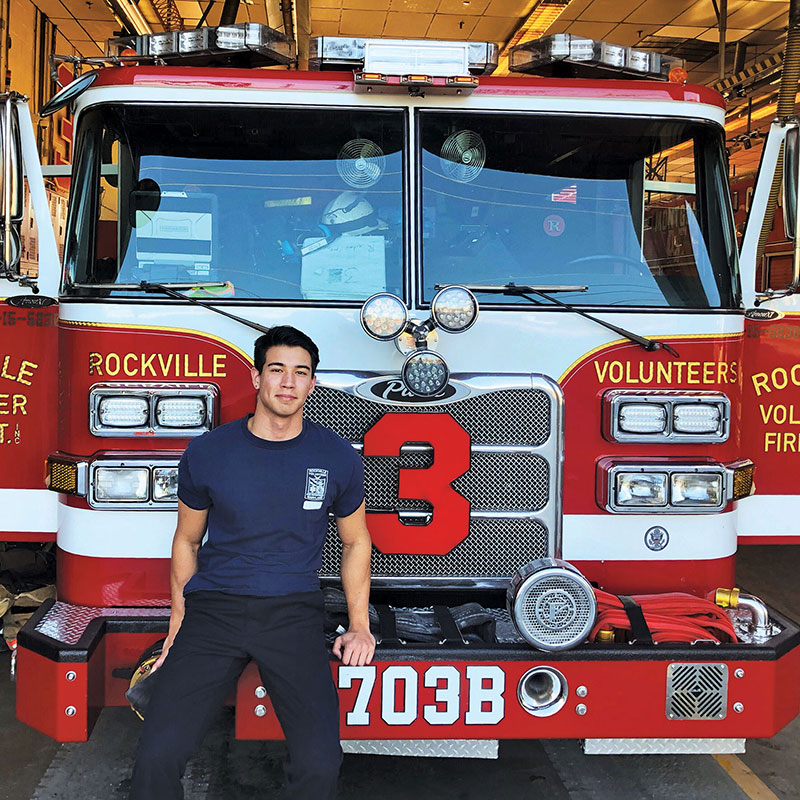 Christopher Hallock sitting on the front bumper of a fire truck